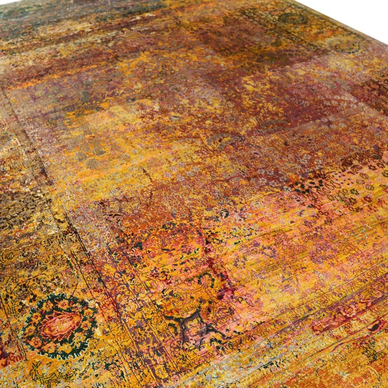 Hand knotted in high-quality luminous silk originating from India this contemporary rug enjoys a unique distressed aesthetic inspired by antique Agra masterpieces, marrying elements of each to achieve this blend of the pomegranate pink-red and gold
