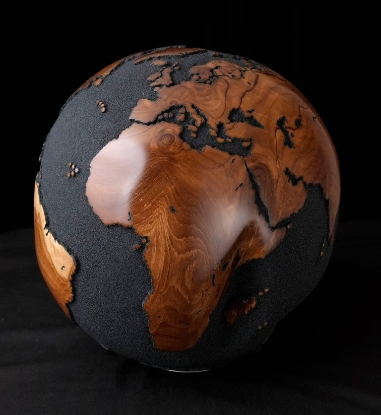 Magnificent wooden globe made of hand-carved teak root, with natural holes in volcanic sand finishing. This engaging piece will definitely be the focal point in any decor setup.   Dimension: 11.81 In / 30 cm Materials: Reclaimed teak root, volcanic