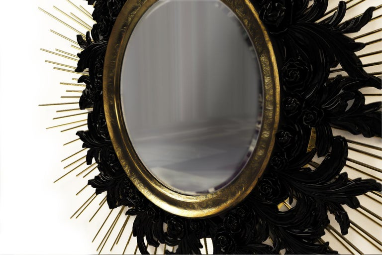 Sunburst mirror features intricate and meticulous gold leafed wood carving with solid brass details and black lacquered wood.