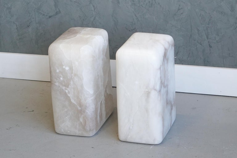 These side or end tables have been hand shaped from a solid block of white alabaster. The unique coloration and veining in the blocks are the focal point of this simple yet captivating piece.   Alabaster color / veining will vary from piece to