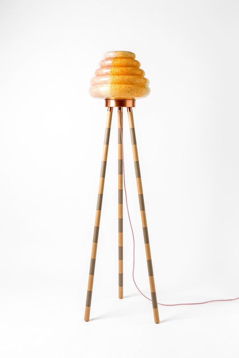 This beehive inspired floor lamp comprises a mixed colored handblown glass shade and different combinations of wood veneer legs and copper. The light is adjustable by the dimmer. Each piece is unique and custom-made.