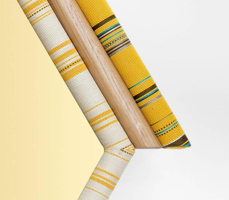Pontiac mirrors are inspired by American Indian tribes. Hexagon version has vibrant colors combined with American white oak and golden tinted mirror. Paul Smith designed Kvadrat fabric has been cut symmetrically and handcrafted on wood and foam. The