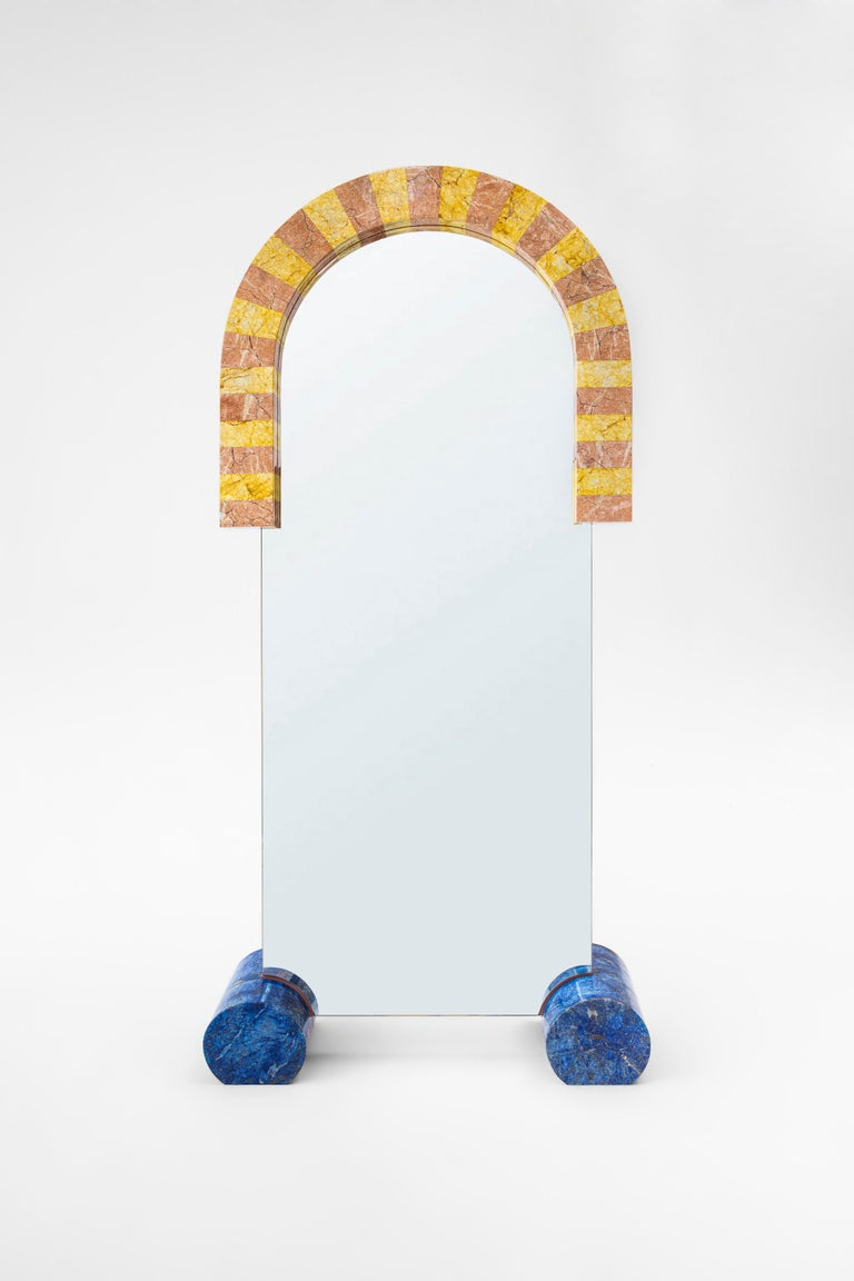 """""""Zaziko Mirror"""" resembles a giant colorful toy made out of marble. Zaziko is handcrafted and assembled with pink and yellow marbles creating a semi arch shape around the clear mirror. 2 giant cylindrical blue painted marble pieces allows support on"""