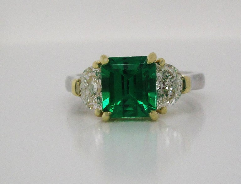 This breathtaking ring is in 18k yellow gold and platinum, boasting a killer deep green emerald center stone flanked by two perfectly matched brilliant white half-moon diamonds. The emerald center is a stunning deep green color and an elegant square