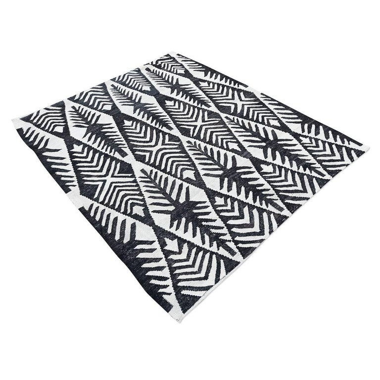 Handmade contemporary wool 100% flat-weave. - Africa collection design. Schematic palmettes drawings that will bring modernity and exoticism to the decoration. - Measures: 1.50 x 1.75 m - Various ranges of intensity of blacks and whites