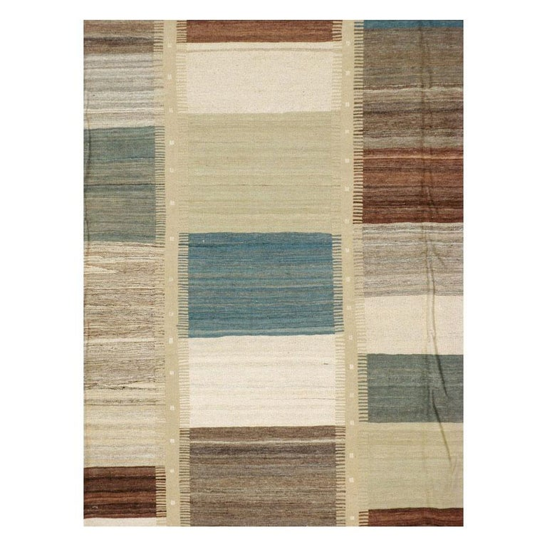 A modern Persian flat-weave Kilim rug handmade during the 21st century. Several rectangles with various tonal colors ranging from light denim blue and grey, ivory, brown, and light pistachio green make up the 5 columns of this pileless room size
