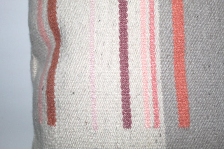 Contemporary handwoven wool throw pillow in pink and grey.   Each color included in this pillow was hand-dyed with natural materials by the artist to achieve the subtle variety in tones. The shades of pink and salmon were created using Lac, a