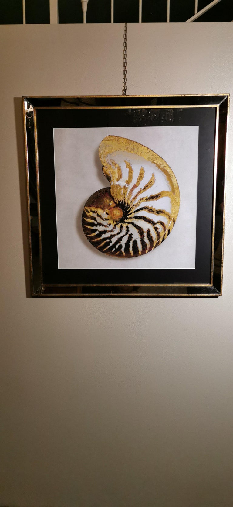 Elegant hand-colored print representing a golden shell. The handcrafted frame is in gilded wood with mirror inserts. This print is made with a special technique called giclée. The giclée printing technique is an individual high definition