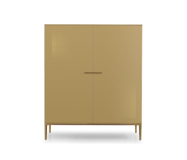 The sideboard is lacquered in RAL7006 beige grey in glossy finish. What looks like a simple sideboard reveals an elegant cocktail cabinet equipment with three drawers and shelves in heat-treated oak and a mirror in the back that gives depth. Led