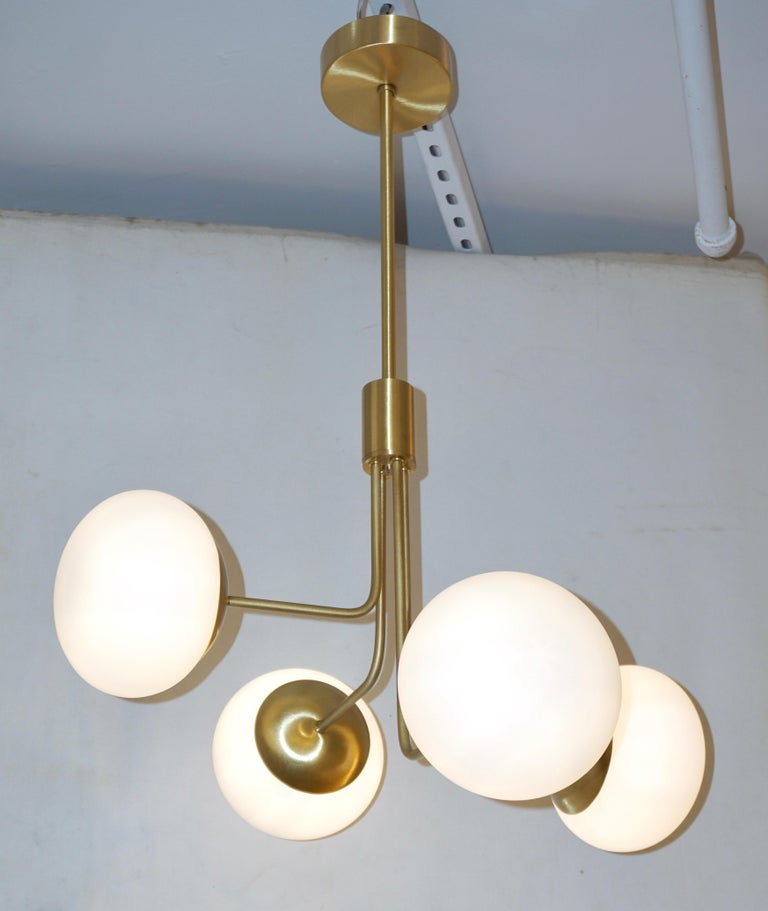 A minimalist Italian structural lighting fixture in Mid-Century Modern design, entirely handcrafted recalling Gino Sarfatti style. The asymmetrically positioned four ovoid globes in white opaline Murano glass give an interesting movement to the