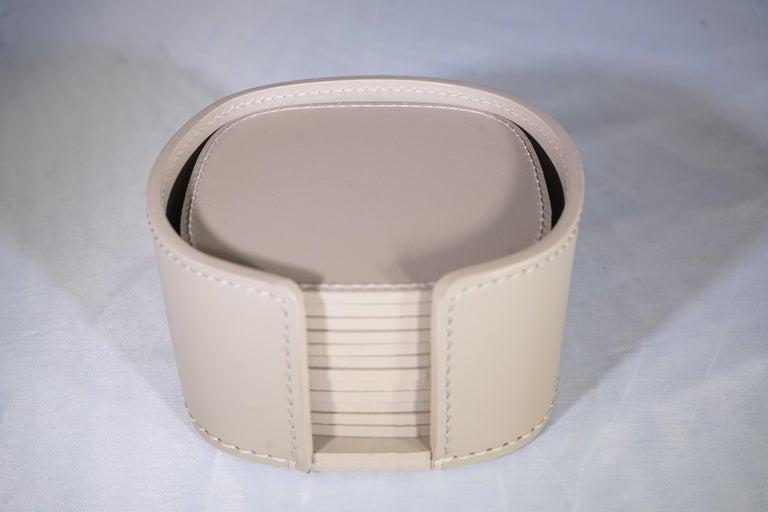 Contemporary Italian Rudi Acquerello taupe leather coaster set with 12 coasters and holder.