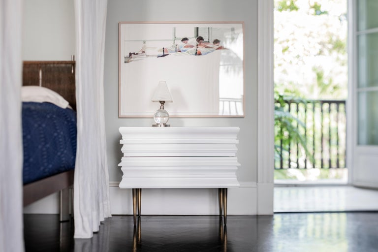 Lacquer white wood moldings are applied to conceal drawers and acting as handles on the nightstand. The process to achieve the finish of the dresser is the result of the combination of multiple moldings. The frame collection is a limited edition.