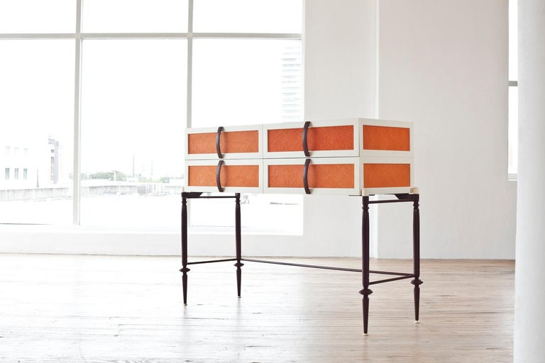 4 drawer dresser in lacquered wood feature appliquéd panels of woven straw while slender metal legs.