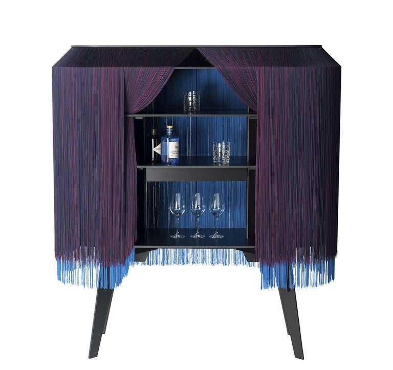 A fun, flirty and contemporary limited edition bar or buffet fully covered with fringes.   This piece features three shelves that are open and accessible on all sides by sliding your hand through the fringe curtains. A central drawer located under