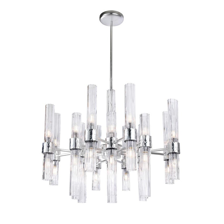 The imposing allure of this precious chandelier results from the combination of its dimensions with the rich yet orderly design characterizing it. Slender, grooved cylindrical lampshades in transparent glass are embedded in the branched metal frame