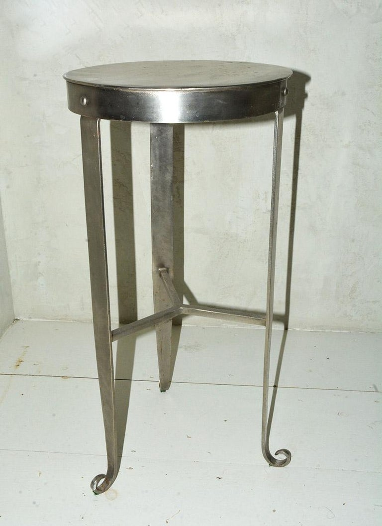 The contemporary nickel-plated steel counter, bar stool or plant stand has three tapered legs with soldered stretchers and ending with cunningly curled feet. The round top has an apron with the legs bolted to it.  Measures: Length between legs 13