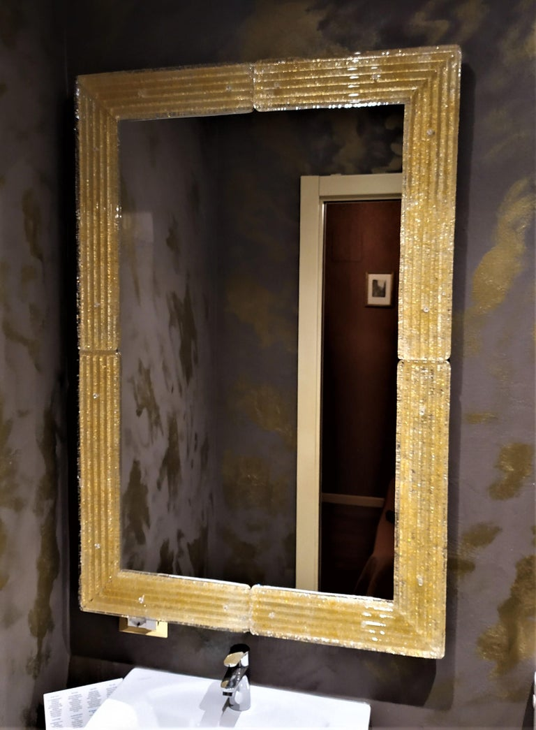 Contemporary style mirror of the 21st century, with the luxurious murano glass frame produced according to the ancient Muranese traditions and processes, frame wich is then cut, shaped and polished in the corners, drilled and fixed to the structure