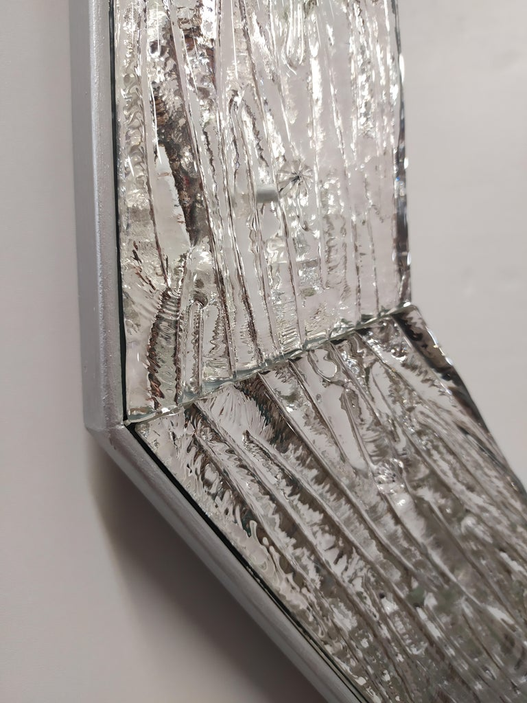 Contemporary style mirror of the 21st century, with Murano glass frame produced according to the ancient Muranese traditions and processes, frame which is then cut, shaped and polished in the corners and then silvered with pure silver, drilled and