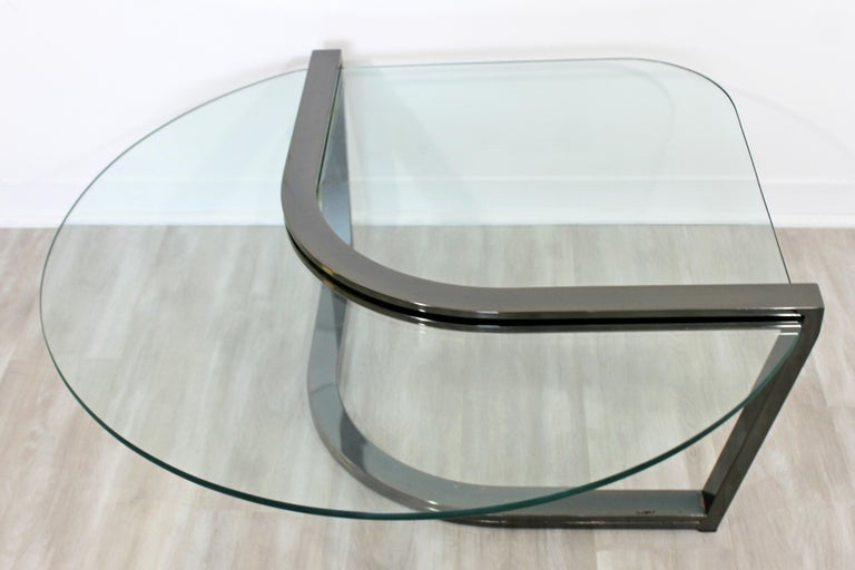 For your consideration is a beautiful, asymmetrical, cantilevered coffee table, with a glass top in a gunmetal base, circa 1980s by Brueton. In very good vintage condition. The dimensions are 44