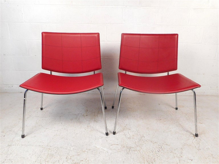 Stylish pair of modern chairs. Very spacious and comfortable seats and backrests. Covered in a red vinyl upholstery, supported by a sleek chrome frame. Made in Italy. This pair would make a great addition to any modern interior. Please confirm item