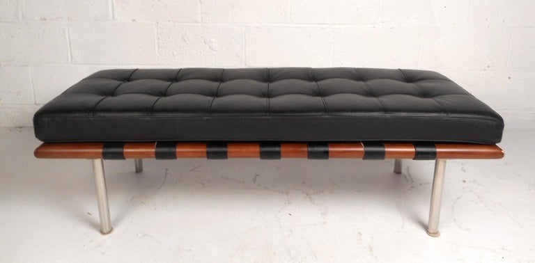This lovely contemporary leather bench has a thick and soft tufted cushion. The comfortable bench cushion is fastened to the sleek teak frame with leather straps to prevent it from sliding off. The entire bench sits atop cylindrical chrome legs.