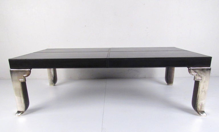 This large modern coffee table features leather upholstered finish with stitched trim and heavy chrome finish legs. The simple midcentury style of this contemporary modern cocktail table makes an impressive addition to home or business seating
