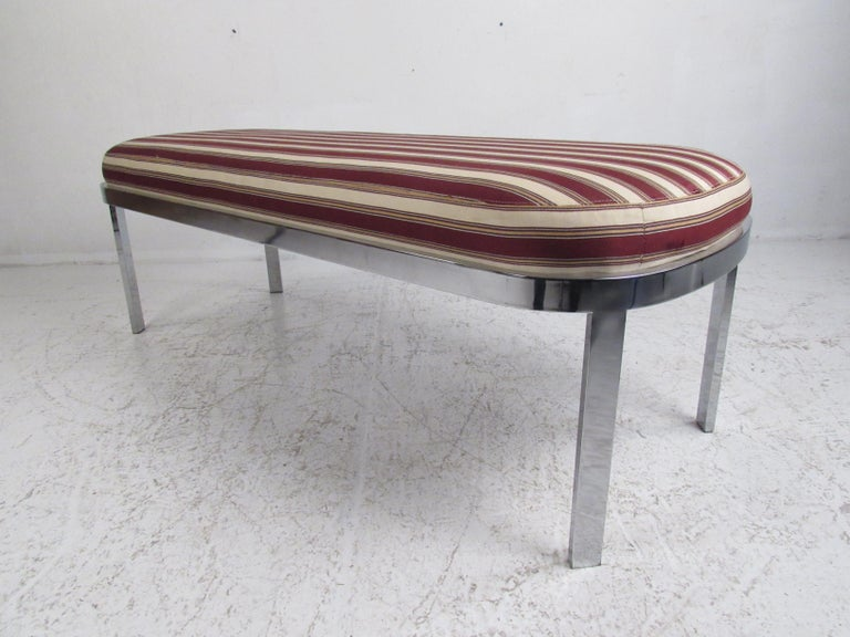 This beautiful midcentury style window bench features a thick padded seat covered in plush striped fabric. A sleek design with a flat bar chrome frame and an oval seat. This stylish bench makes the perfect addition to any entryway, bedroom, or