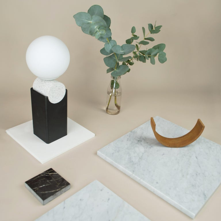 Monument Lamp - Circle Version 2 has a blackened steel base with a cast Jesmonite cylinder and a matte opal glass globe.   Inspired from architectural forms such as monoliths and monuments, implemented through the design with heavy, robust materials