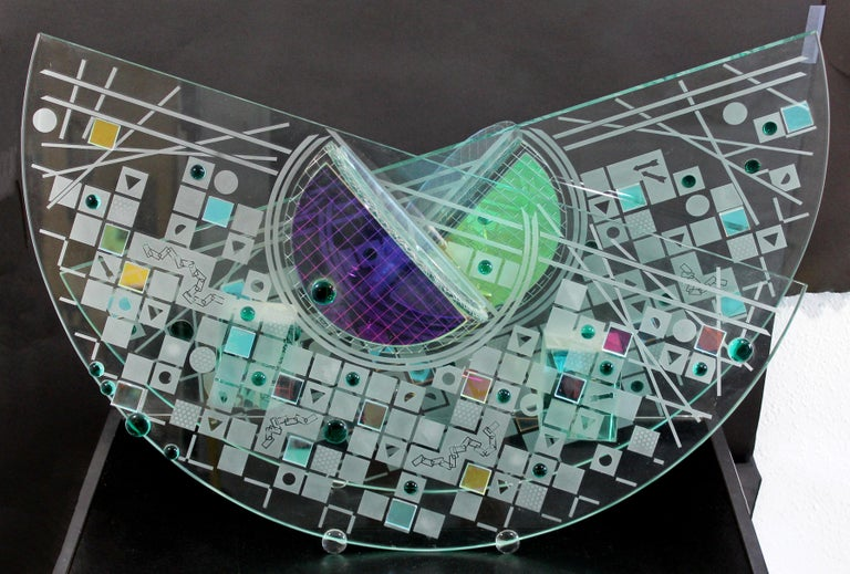 For your consideration is a luminescent, abstract glass table sculpture in the Memphis style, circa the 1980s. By renowned glass artist Toland Sands. In excellent condition. The dimensions are 30