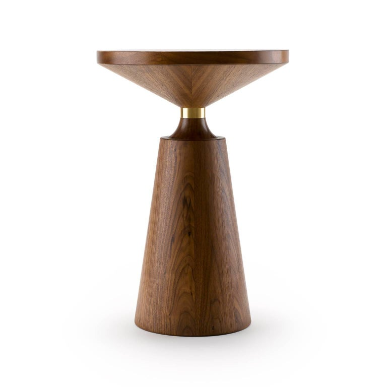 Turned by hand and using both solid and veneered timber, the Nicole Side Table has a simple but graphically striking Silhouette punctuated by the metal collar. The Nicole Side Table is shown here in natural oiled walnut with natural brass (front)