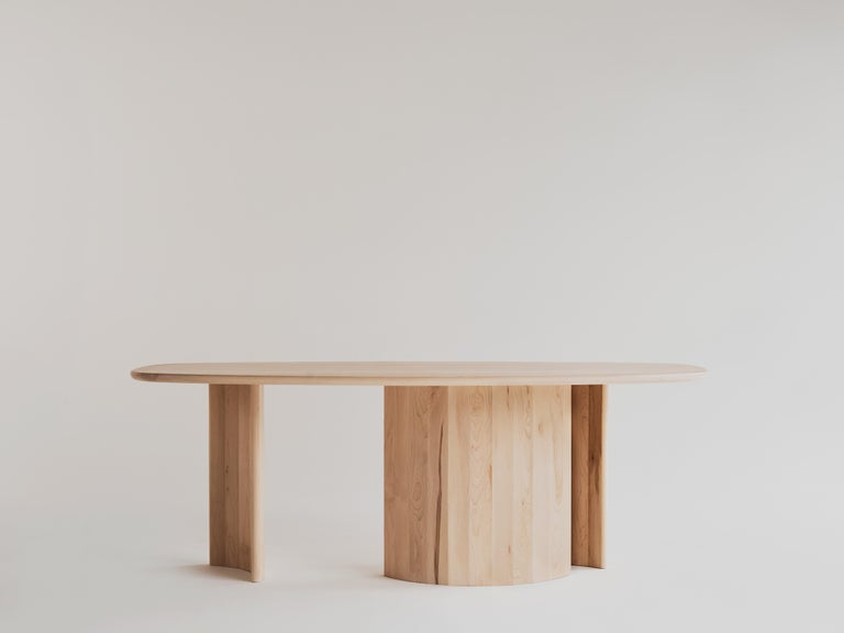 Dining table for Richard by Campagna in maple.  This sculptural, contemporary wooden dining table features a free flowing, organic top and faceted, arc-shaped legs. The interaction of the three uniquely curved legs creates moments of shifting