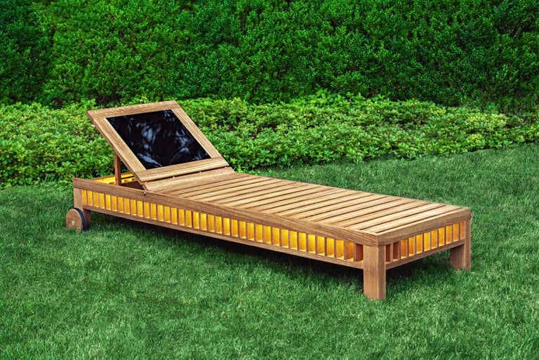 This wooden slatted solar lounger integrates a photovoltaic panel in its adjustable backrest. The panel, which reflects the surroundings in its mirrored surface, collects enough power to illuminate lights inside the body of the lounger at fall of