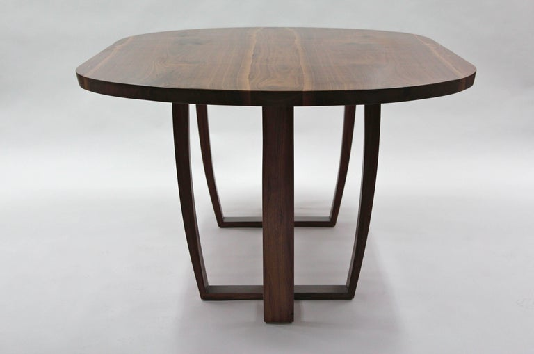 The top is made from two pieces of inverted, mirror image (bookmatched)  American black walnut carefully cut into a central slab of walnut, the shape of the logs live edge is inset into the tabletop, giving visual reminder of the tree that it came