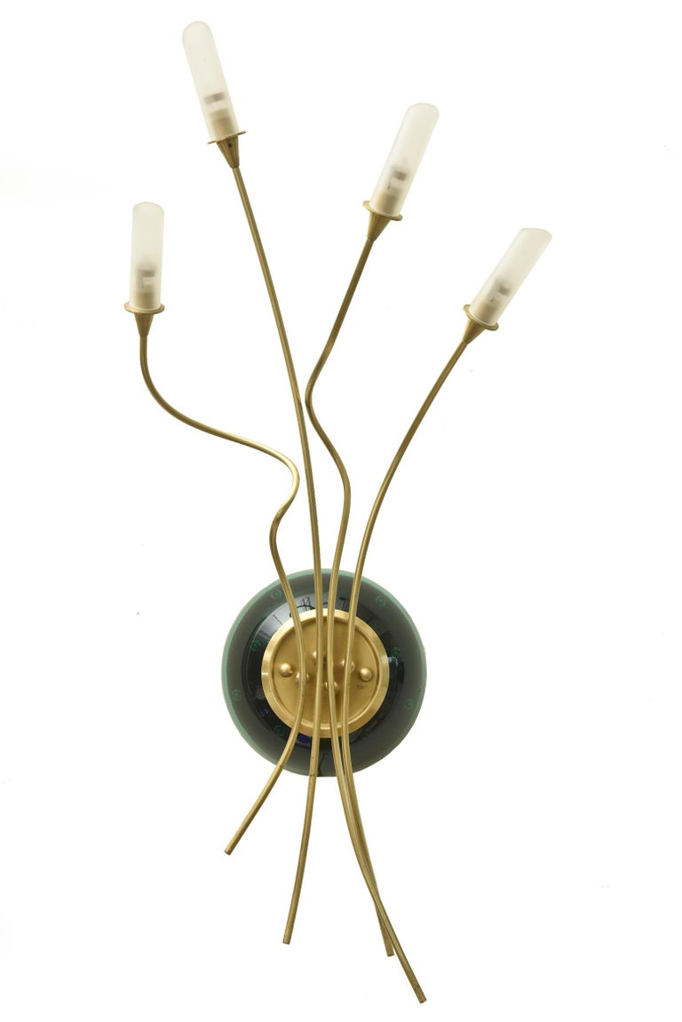 This pair of custom contemporary combination of Murano glass infinity lights and gold plated brass armature make for sculptural wall sconces. Their interested arms create a movement on the wall. The emerald green glass middle portion when lite up