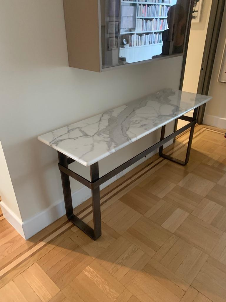 The Axel Console, an original design, is a contemporary Minimalist patinated stainless steel and marble top console designed and produced in Vermont by Scott Gordon. It features a satin stainless steel base with a hand applied patina which supports