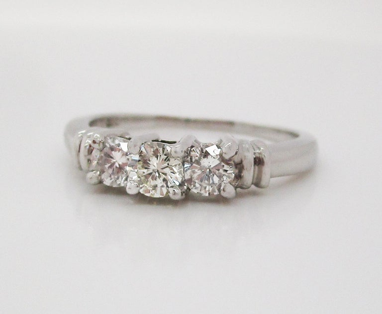 This gorgeous three stone diamond engagement ring is in bright white platinum and has a gorgeous contemporary look! The three diamonds in this ring are set in a stepped design with an architectural under-gallery. The stepped design of the ring