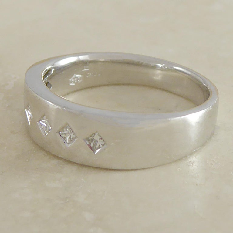 A lovely diamond set ring that works just as well as a wedding or eternity band as it does an every-day dress ring.  The band is plain polished 18ct white gold set with five princess cut diamonds in rub over mounts and arranged in a harlequin