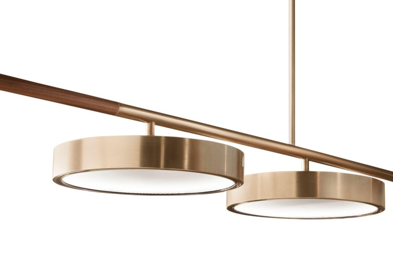 The QD09 hanging lamp is made with brass, wood and thin ribbed glass. It is customizable in its height and length therefore adaptable to many spaces from a meeting room to a dining room or a kitchen island. Measures: The standard length is 250cm and