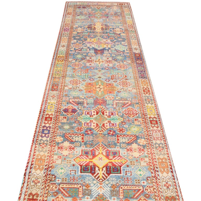Originating from Rajasthan, this contemporary tribal rug is hand knotted with the classical Turkish knot symmetry, enjoying a Cascade of lively red, golden-yellow, green, purple, and blue colorways throughout the equally intricate field design,