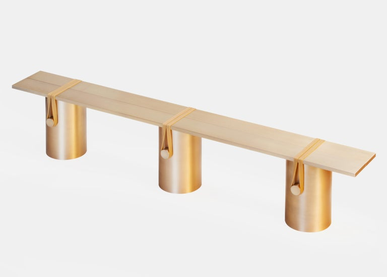 The RB02 - Anodised bench is a sculptural composition made of eight brushed aluminum parts. Two plates are leaning onto three tubes; held under tension with three cylinders and polyurethane rubber bands. The bench is anodised with a light bronze