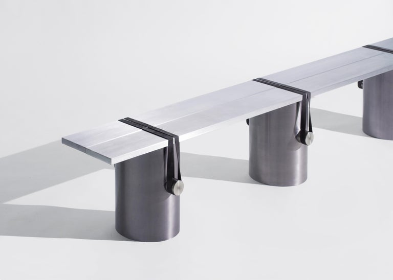 The RB02 bench is composed of two brushed aluminium plates leaning onto three lightly brushed steel tubes; held under tension with polished stainless steel cylinders and black rubber bands.   This radical assemblage is the result of a continuous