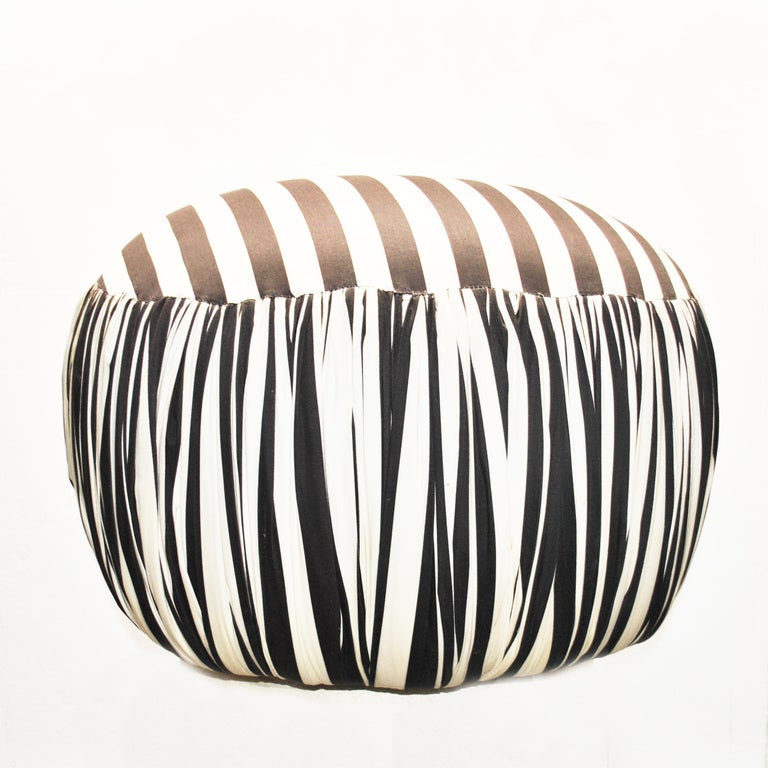 A round contemporary pouf or ottoman in black and white striped fabric with pleated sides.