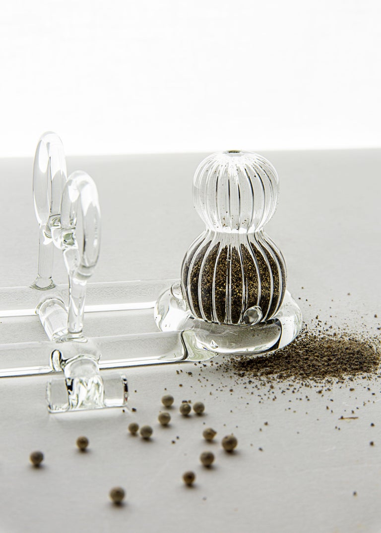 Salt and Pepper shaker from SiO2 Tableware collection   Small Salt and Pepper shakers in striped glass that can be settled in their graceful base with handle.  Part of the SiO2 tableware collection, it has an aesthetic linked to the world of