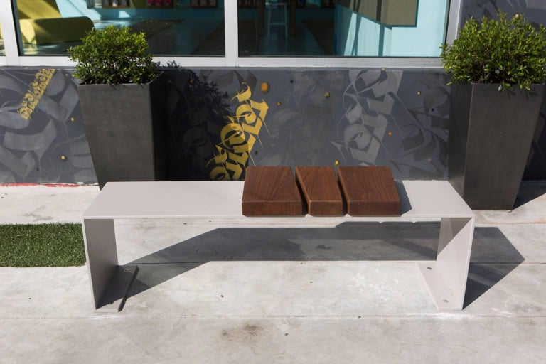 This bench was originally commissioned for an exterior public art space in Wynwood, Florida. It is shown here in aluminium with a flat grey powder coated finish and solid Ipe wood. This piece is available in a wide range of colors, sheens and other