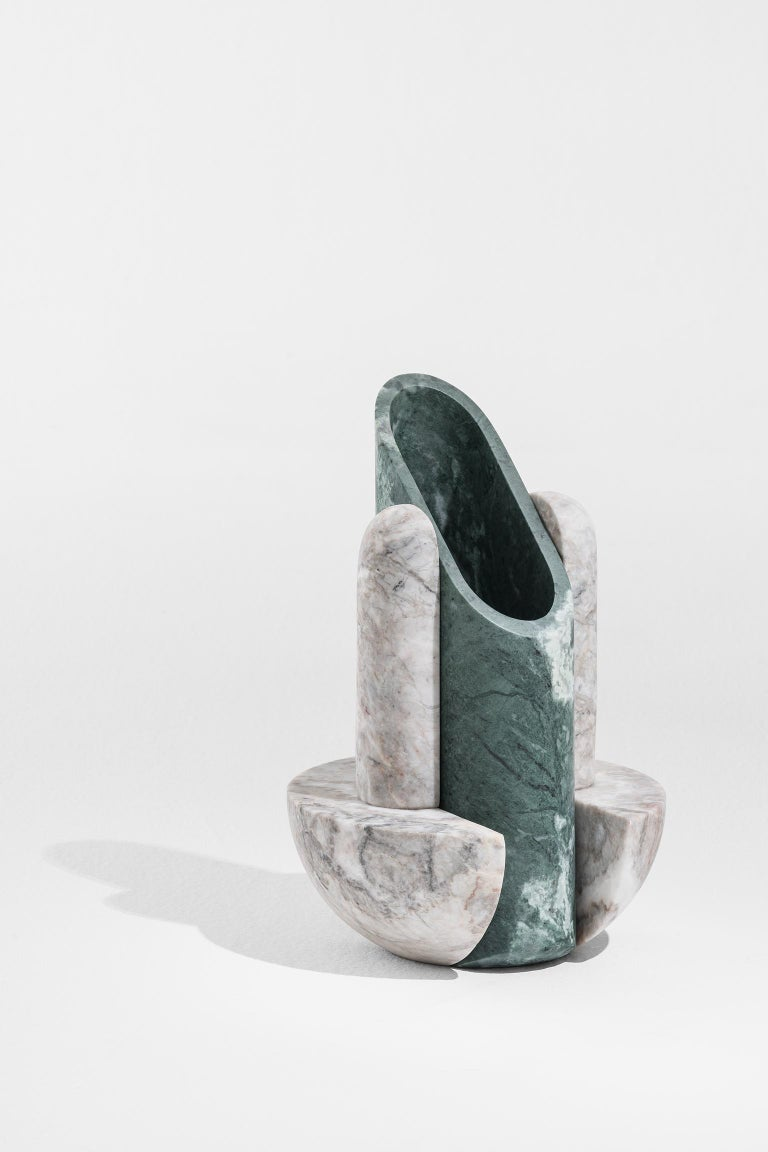 Geometric sculptural vase in Rosa Carnico and Verde Carnico marble, Simultanea collection. Centripetal, centrifugal and movement forces are channeled into stone forms and a rotation on the axis become a vase, while an inclined cut suggests a