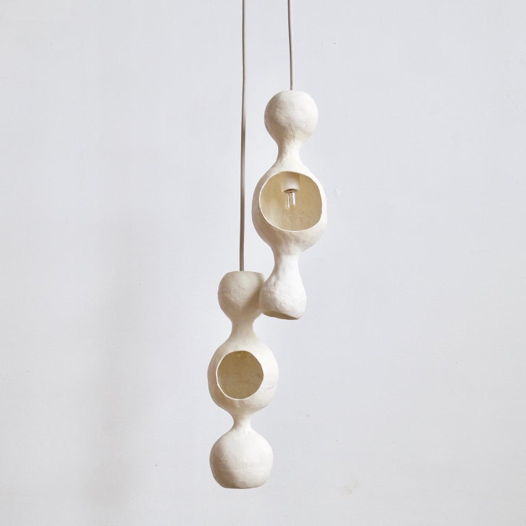 White Bowerbird couple is a contemporary double-shell hand-built ceramic pendant lamp finished in a matte white glaze with a warm glow reflecting off of a round joyful form. Each shell is individually hand formed and unique, creating a pleasant
