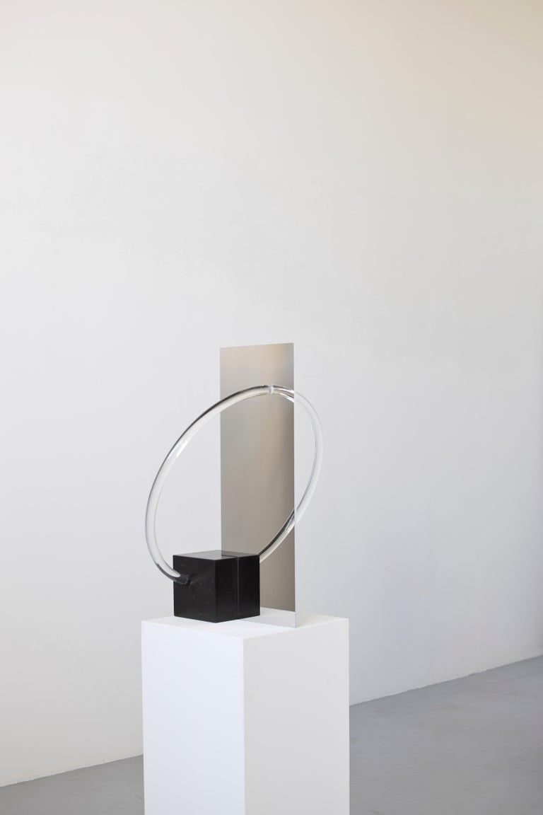 Elusive 01 A beautiful piece exploring the line between visible and invisible: half table lamp, half mirror, half sculpture. By Maximilian Michaelis.  Belgium bluestone, polished stainless steel, acrylic glass, Led Measure: 56 x 46 x 29 cm.