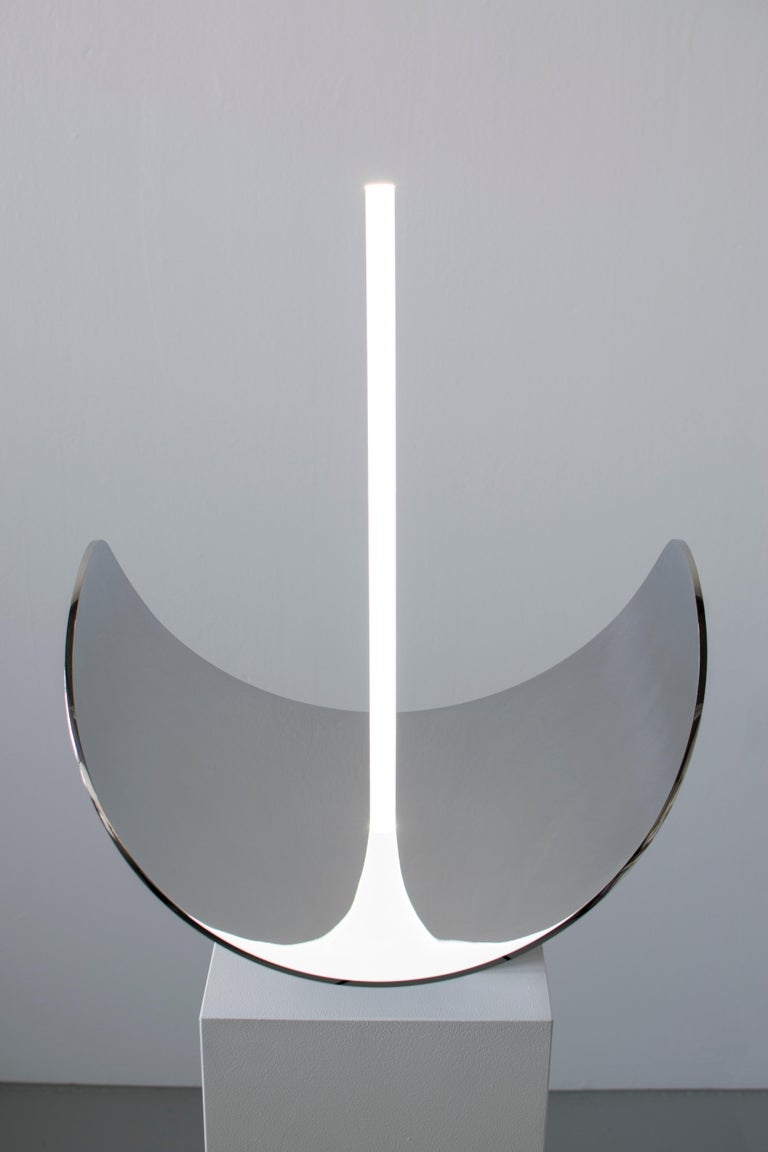 Elusive 09 A beautiful piece exploring the line between visible and invisible: half mirror, half floor lamp, half sculpture. By Maximilian Michaelis.  Blue stone, polished stainless steel, acrylic glass, Led Measure: 60 x 50 x 50 cm.