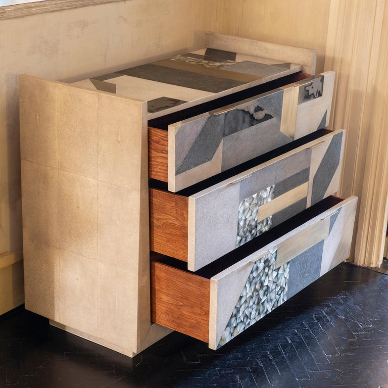 Contemporary three-drawer chest of drawers covered with geometric design of natural / light grey / grey shagreen plus black and light green penshell, brass details, France.