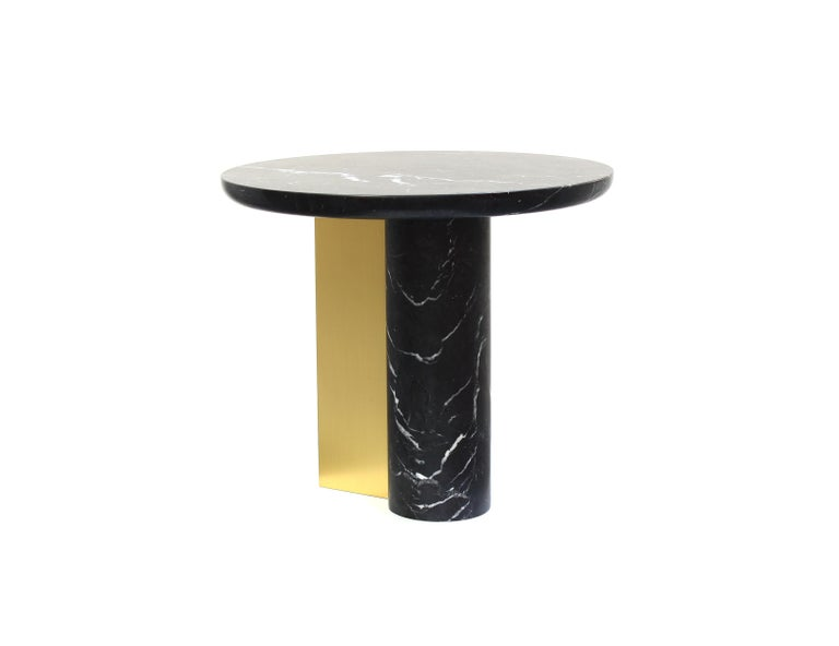 This monolithic side table has an elegant and refined silhouette. An off-balanced cylindrical solid base attached to a circular top is supported by a folded brass plate enlightening and balancing the piece. The simple elegance of essential forms